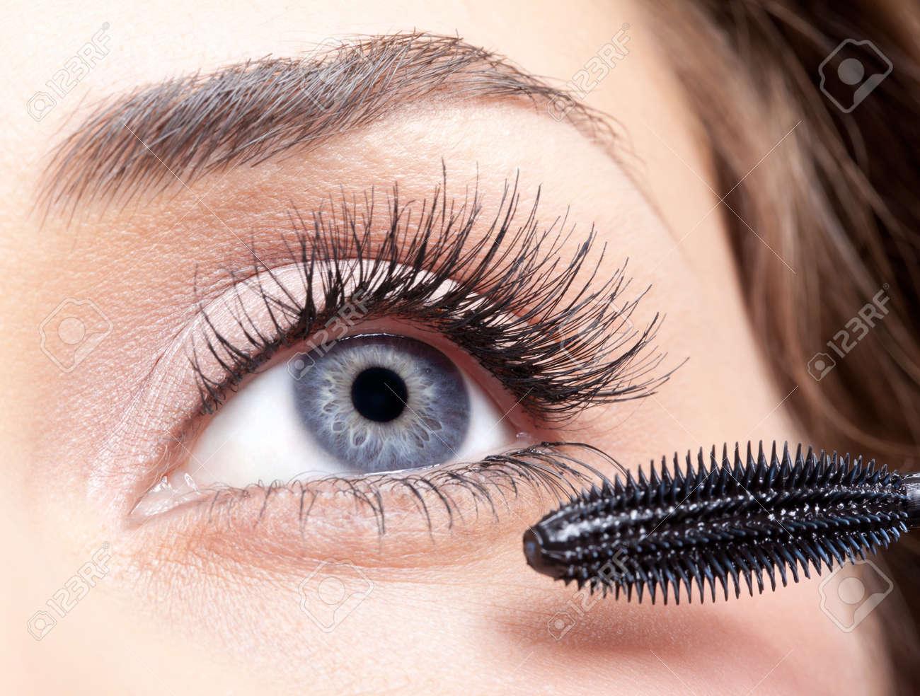 Young beautiful woman applying mascara makeup on eyes by brush - 16826536