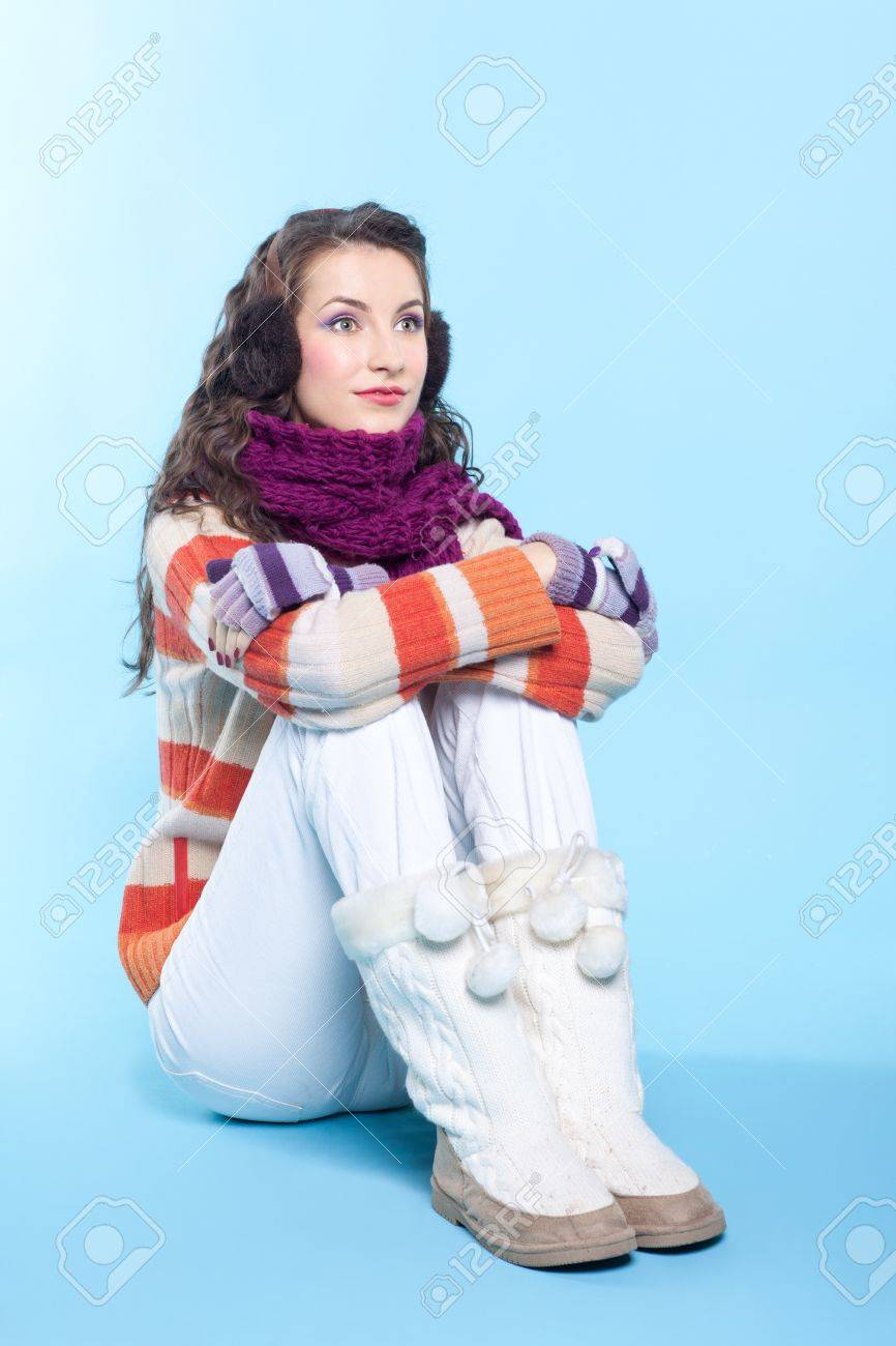 Young pretty woman in winter dress sitting on blue background Stock Photo - 17098956