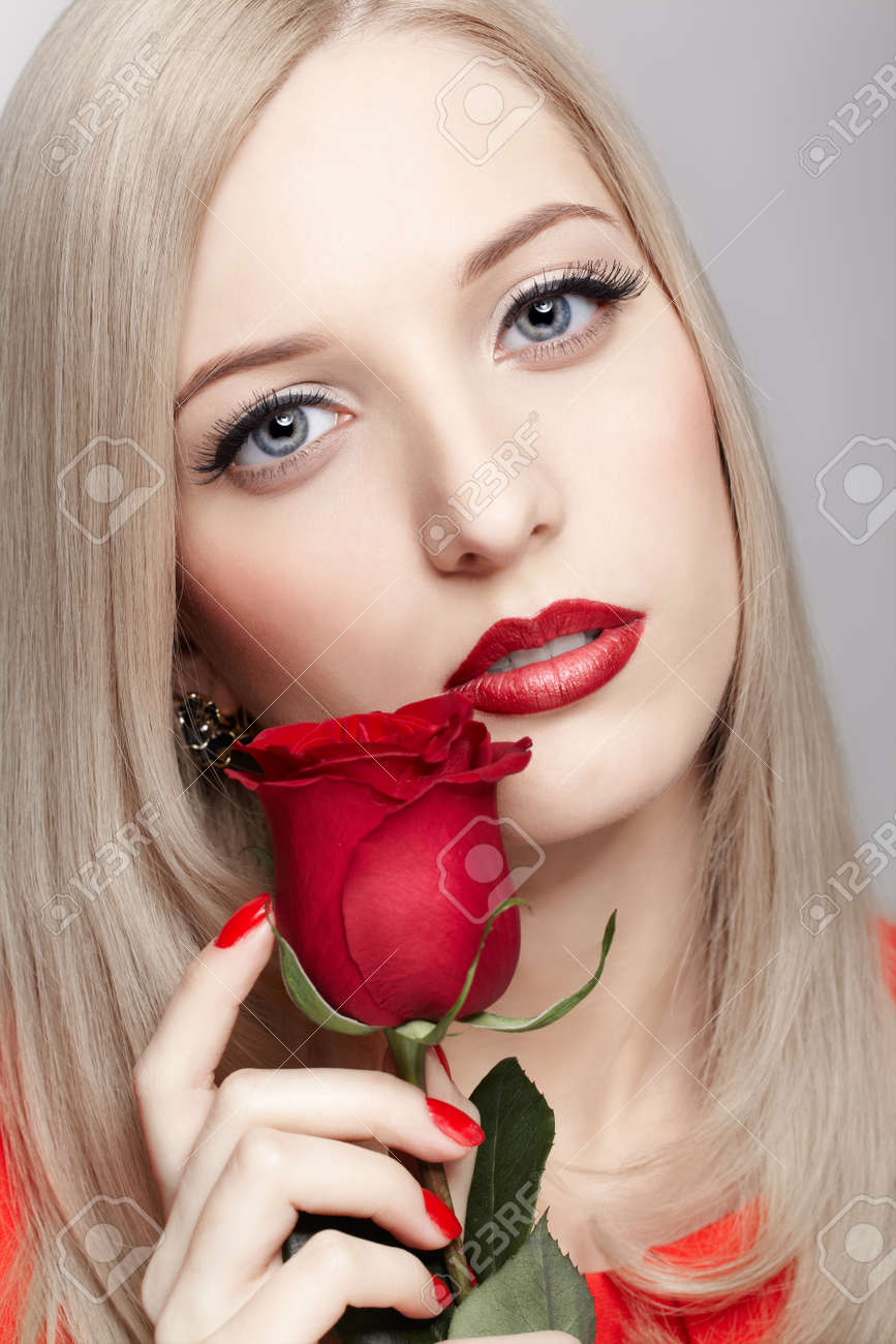 portrait of young beautiful blonde woman in with red rose flower in hands Stock Photo - 17566719