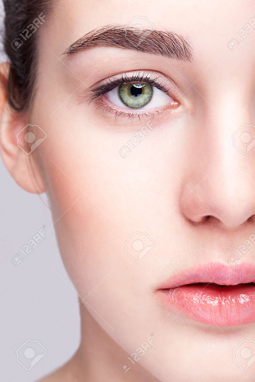 Closeup shot of female face with day makeup and green pistachio colour eyes - 37028674
