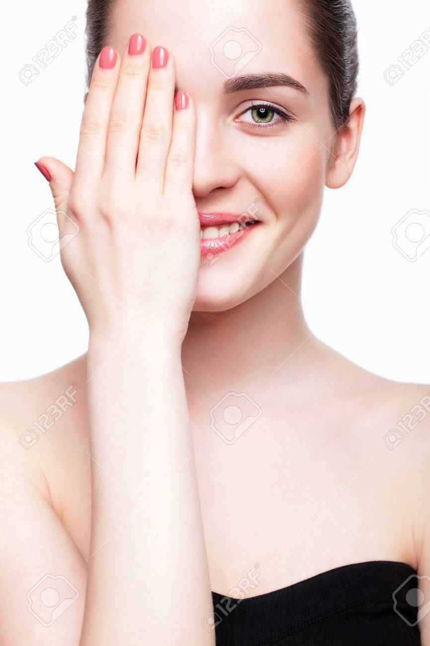 Green-eyed young beautiful woman in black dress closing eye by hand and smiling - 37028724