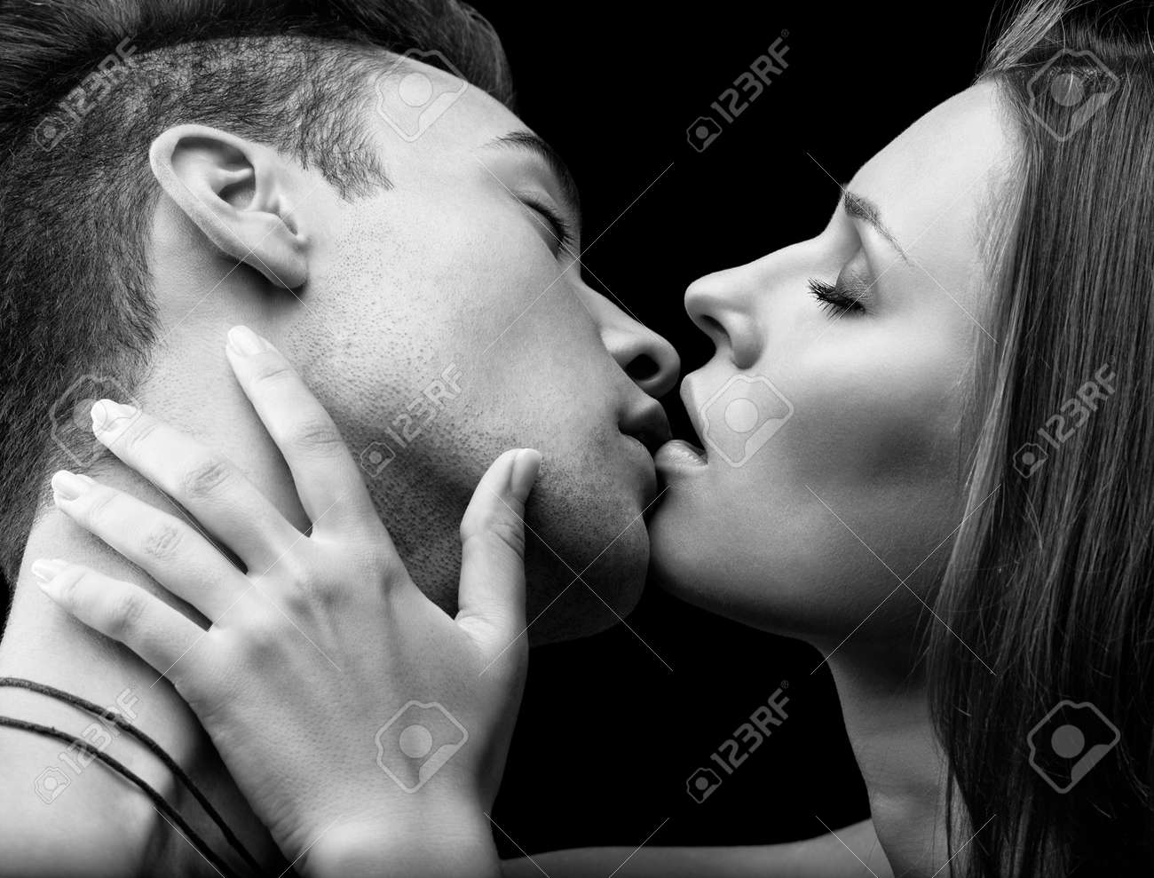 Stock photo young couple of lovers kissing on black background