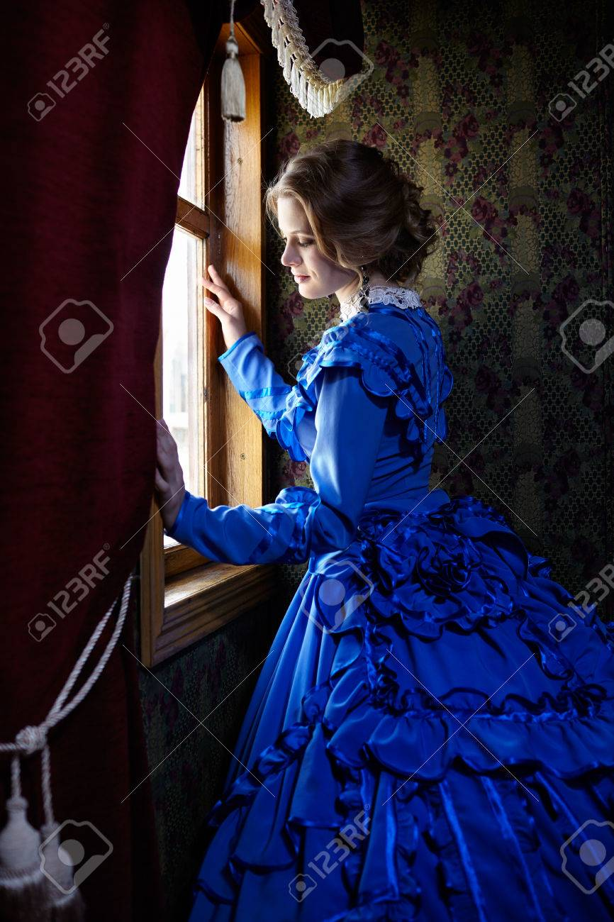 Young woman in blue vintage dress late 19th century standing near window in coupe of retro railway train - 45139077