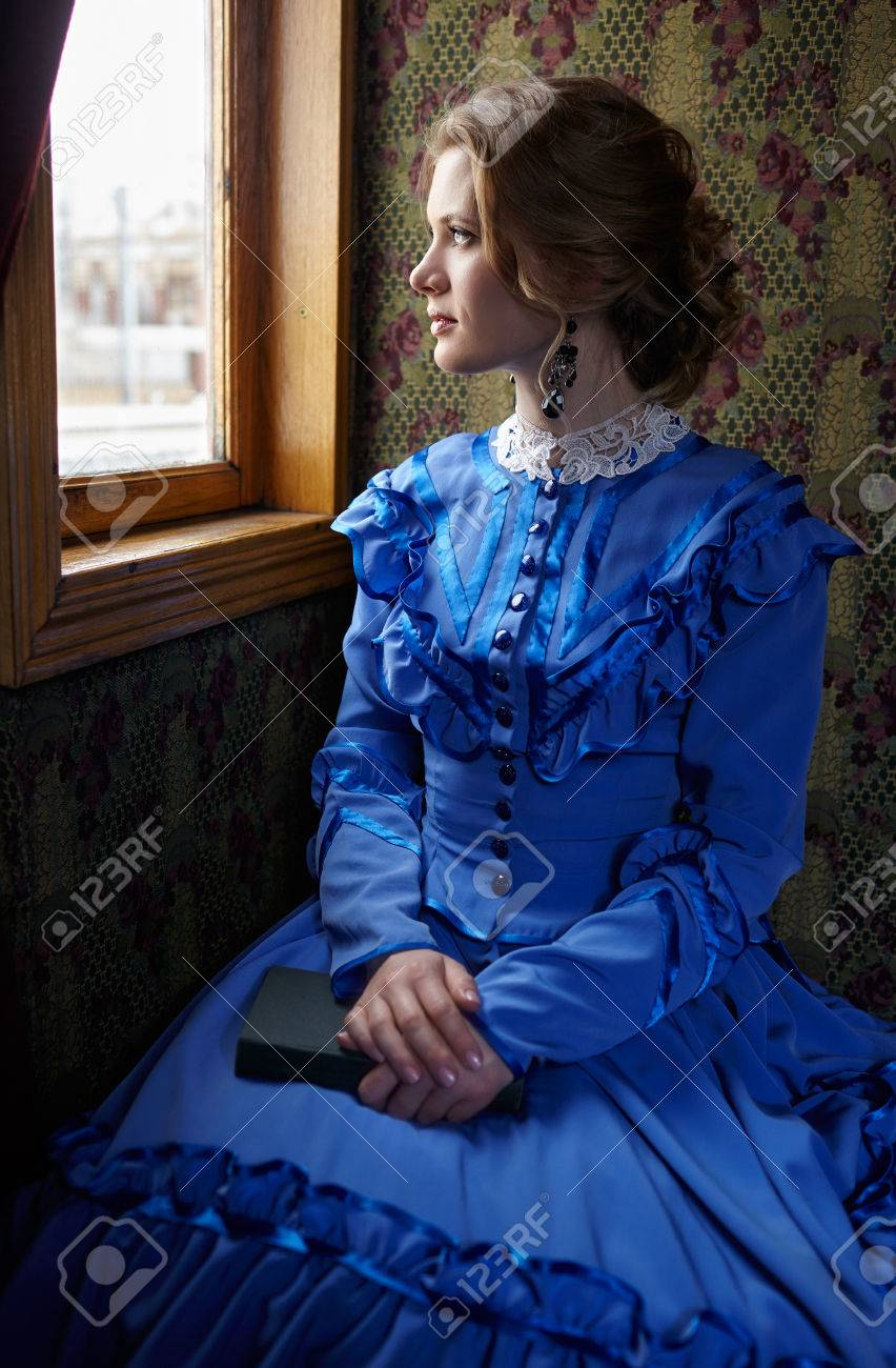 Young woman in blue vintage dress late 19th century sitting with book in coupe of retro railway train and looking out the window - 45139079