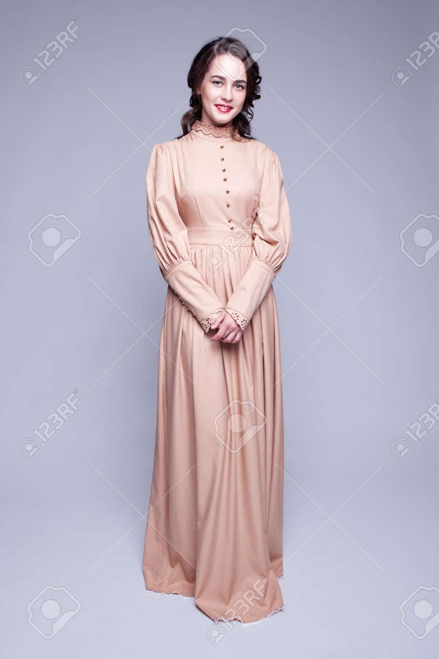 55fb0dbac0 Ritratto a figura intera della giovane e bella donna in abito beige retrò  con il trucco del giorno e gli occhi di colore verde pistacchio