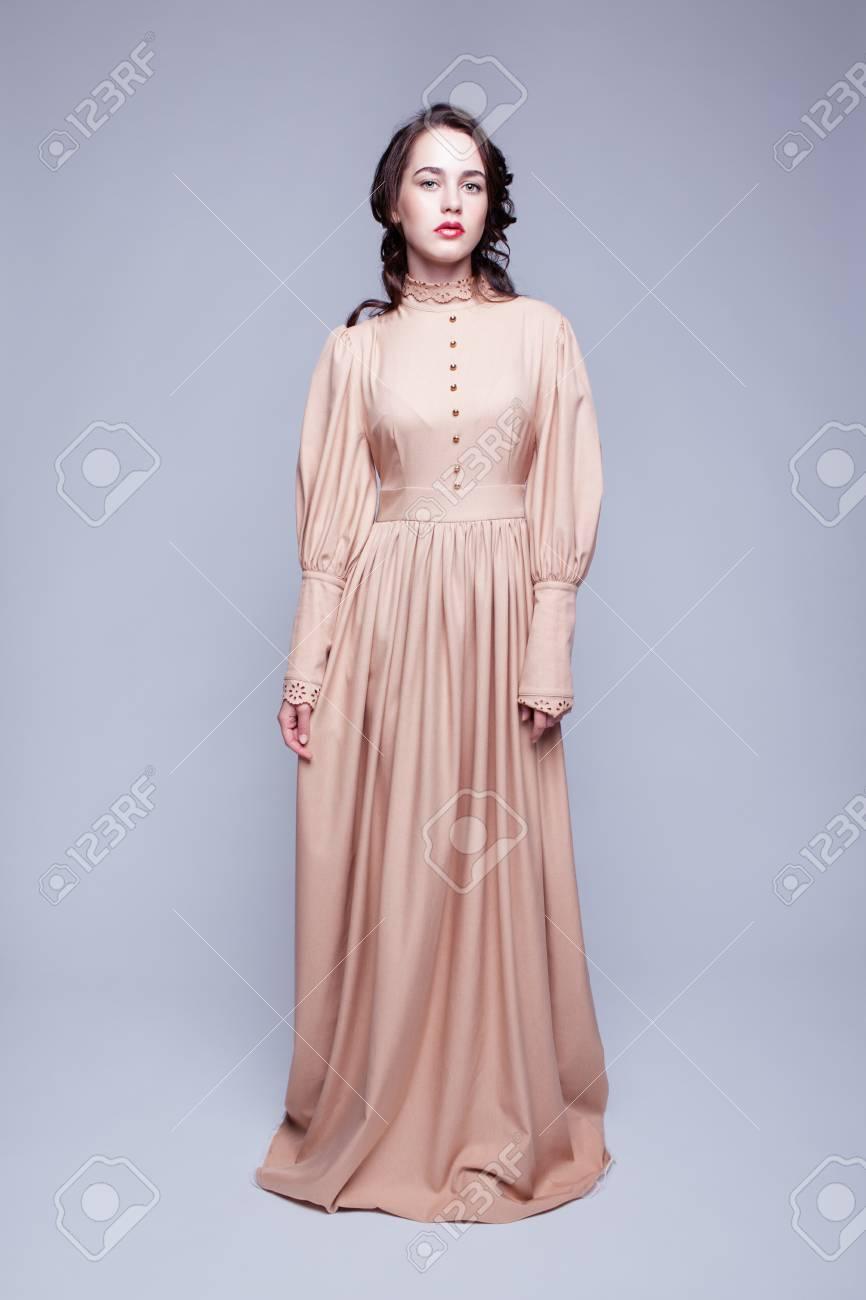 2121c9b4da Full-length ritratto di giovane donna bella in abito beige retrò con il  trucco giorno e gli occhi color verde pistacchio