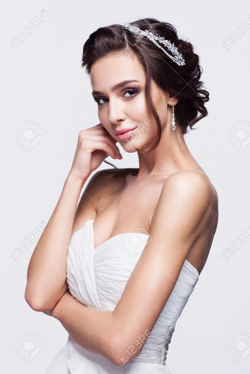 Portrait of beautiful young brunette woman bride with hand near face in white Wedding Dress on light gray background - 50255204