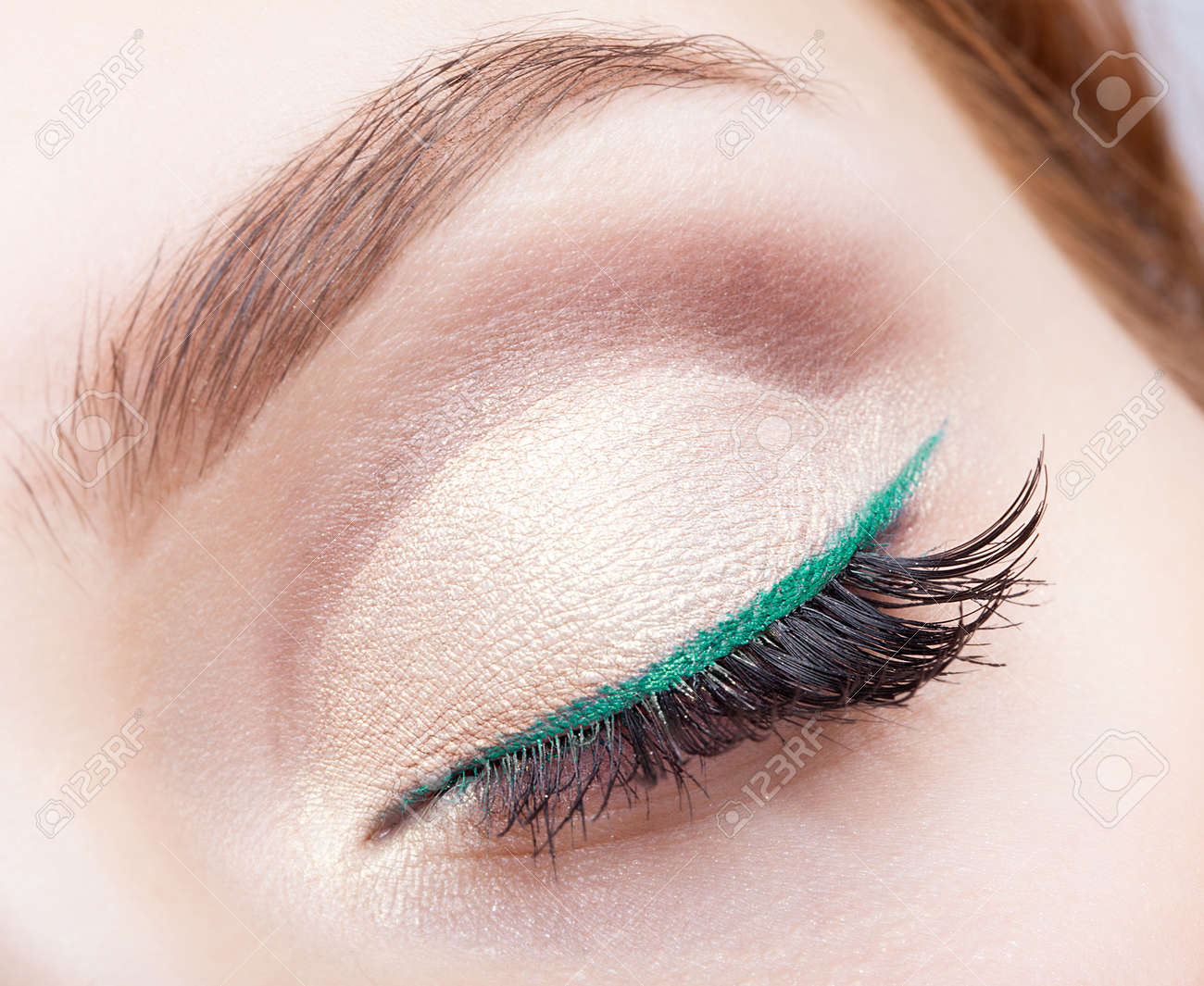 Closeup shot of female face makeup with closed eye and green eyeliner - 55841606