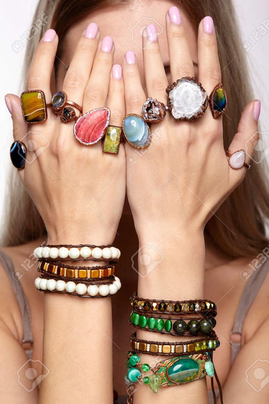 f4102f7d8d47 Foto de archivo - Manos de la mujer joven con múltiples pulseras y los  dedos con muchos anillos con piedras