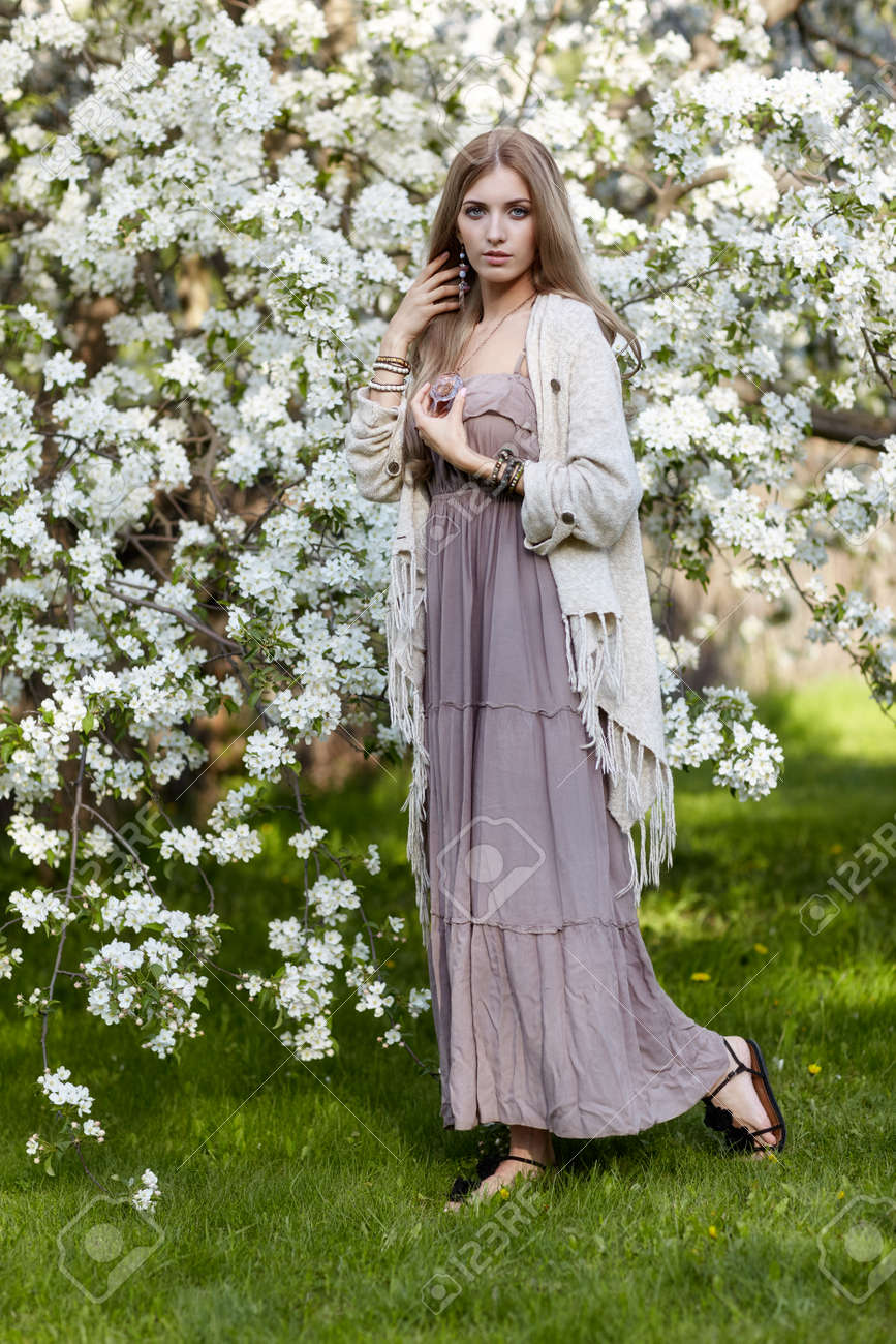 Beautiful young woman in long dress boho style on green grass under apple tree in blossom in Spring garden - 59285854