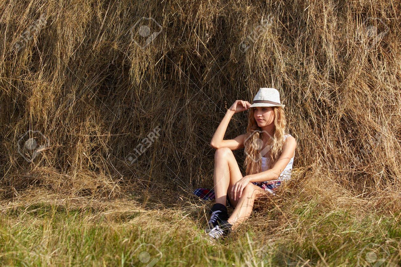 Jeune Fille De La Campagne Blonde Dans Le Chapeau Assis Pres De Haystacks Banque D Images Et Photos Libres De Droits Image 64388249