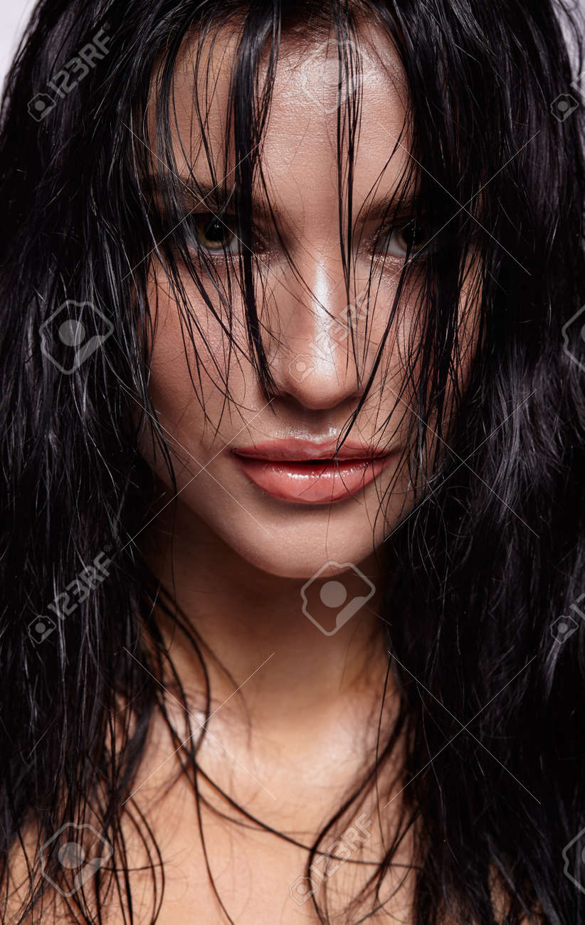 portrait of a young brunette woman with hining wet make-up and shiny