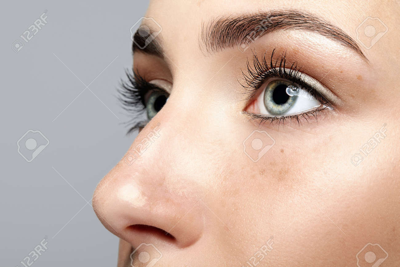 Closeup macro portrait of female face. Human woman open eyes with day beauty makeup. Girl with perfect skin and freckles. - 84110406