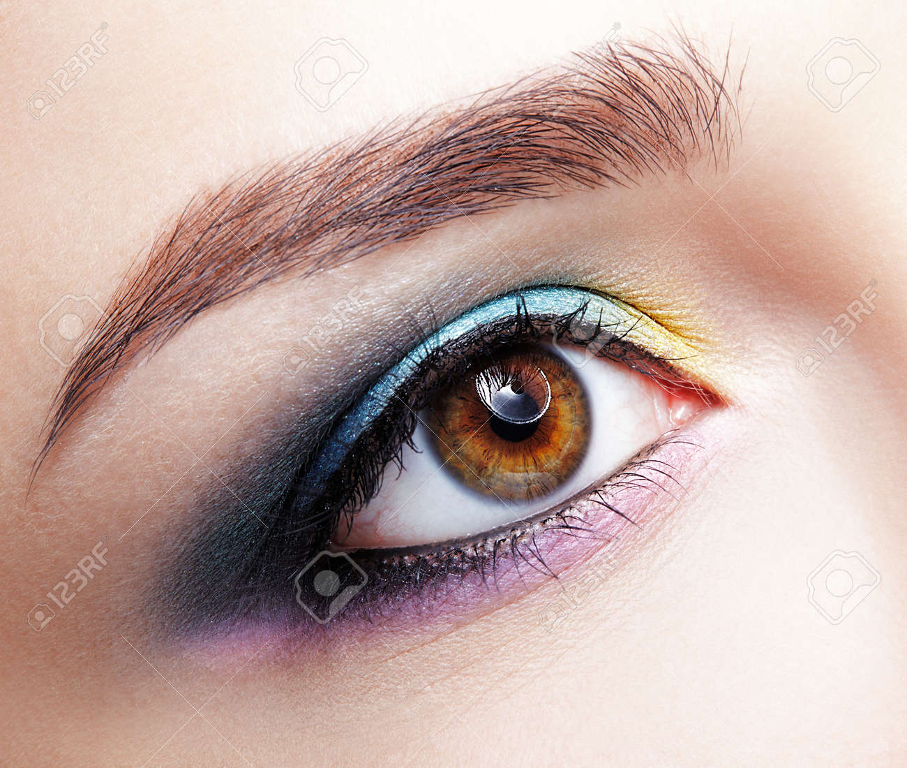 Closeup macro shot of human female eye. Woman with natural evening vogue face beauty makeup. Girl with perfect skin and lilac - blue - yellow eyes shadows - 88757346