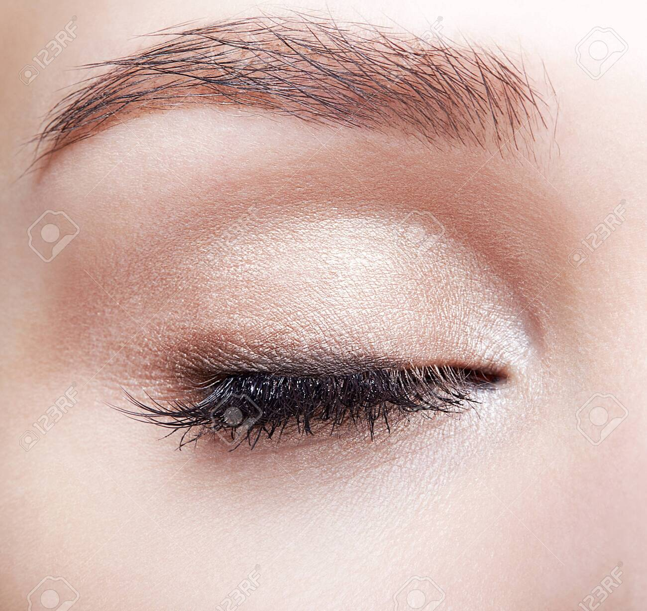Closeup macro shot of closed human woman eye. Female with natural eyes makeup - 121765065