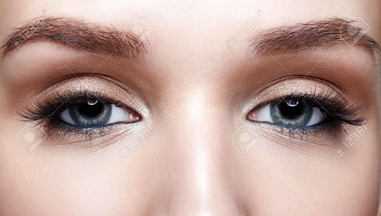 Closeup macro shot of blue human woman eye. Female with smoky eyes makeup - 121765067