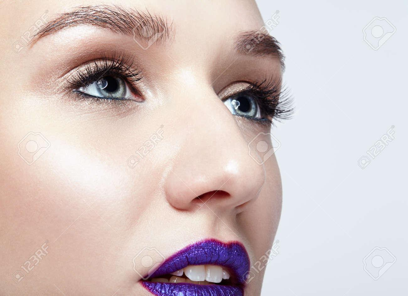 Closeup macro shot of human woman face. Female with natural eyes makeup and bright violet lips - 121765031