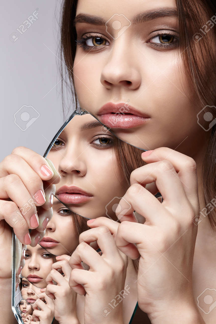 Girl with a shard of the mirror. Female with mirror shard in hand posing on gray background. Multiple reflections in mirror splinter. - 140336520