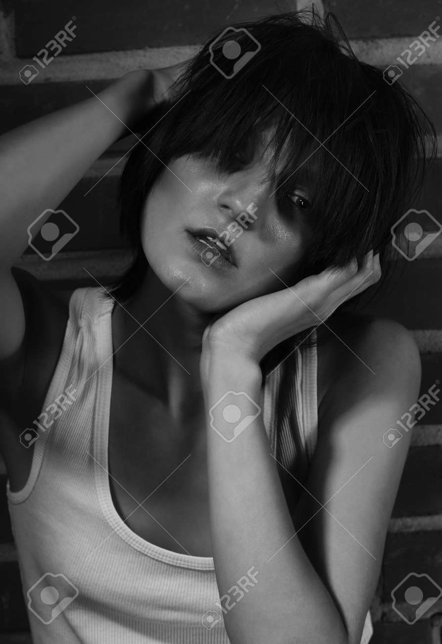 Androgyny female model in Heroin chic style near brick wall. Old style tinted image - 159580392