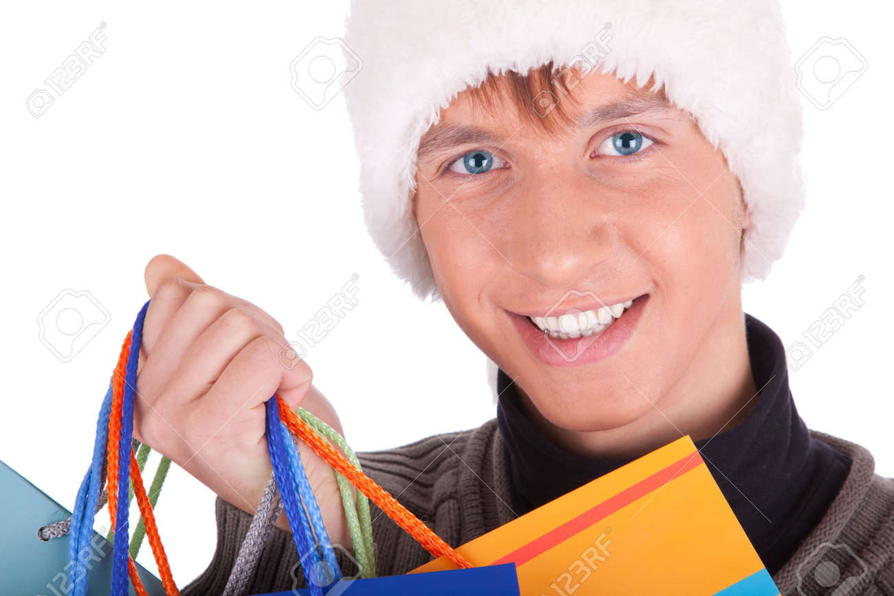 Stock Photo - young man in a Santa Claus hat handing gift bags - 5768673-young-man-in-a-Santa-Claus-hat-handing-gift-bags-Stock-Photo