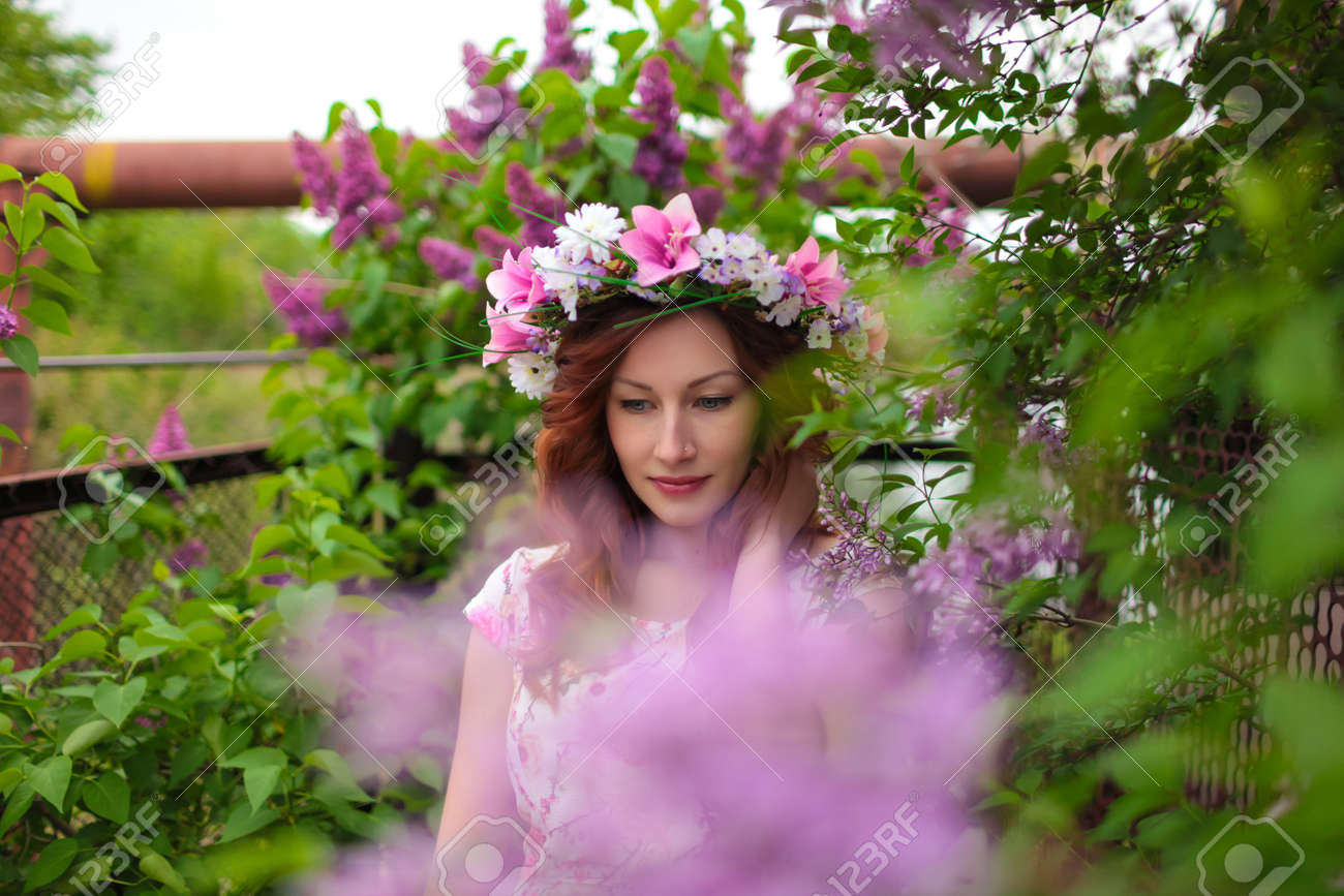 Banque d\u0027images , Belle femme dans une couronne de fleurs près de l\u0027arbre  lilas en fleurs. Cheveux rouges, les lèvres.