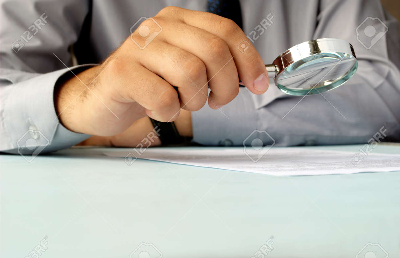 Businessman looking through a magnifying glass to documents - 14866993