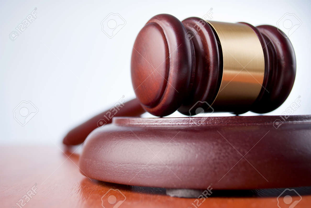 brown gavel with a brass band on a gray background Stock Photo - 17163546