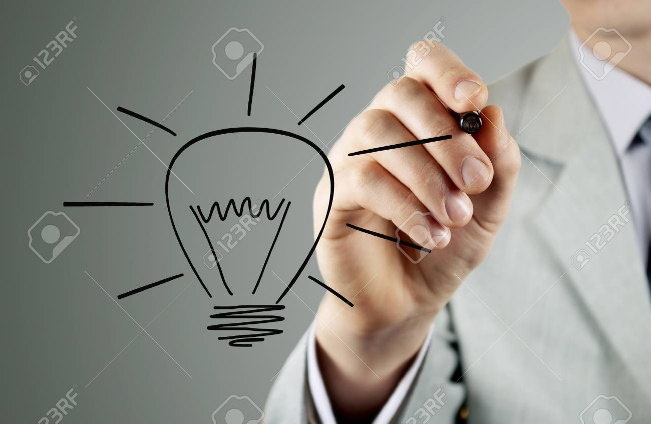 Businessman draws a light bulb, the symbol of the idea of Stock Photo - 18540415