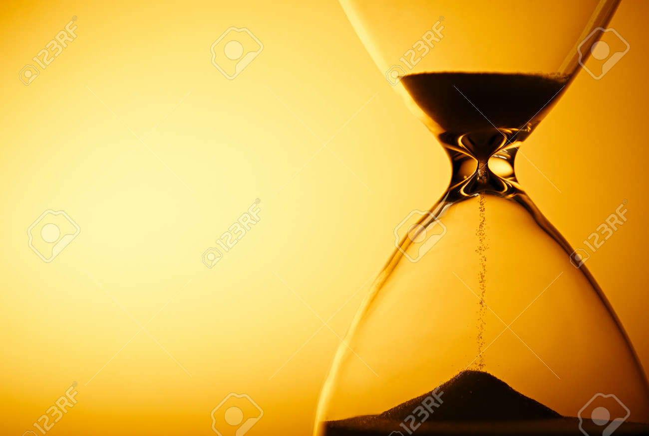 Sand passing through the glass bulbs of an hourglass measuring the passing time as it counts down to a deadline or closure on a yellow background with copyspace - 30765483