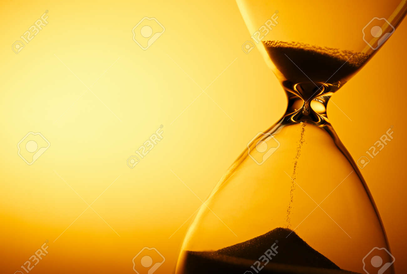 Sand passing through the glass bulbs of an hourglass measuring the passing time as it counts down to a deadline or closure on a yellow background with copyspace - 30765380