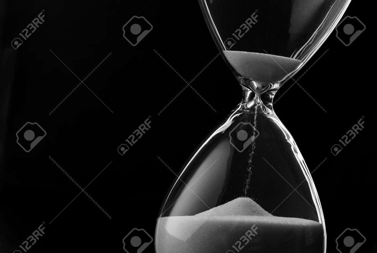 Sand running through the bulbs of an hourglass measuring the passing time in a countdown to a deadline, on a dark background with copyspace - 30765382