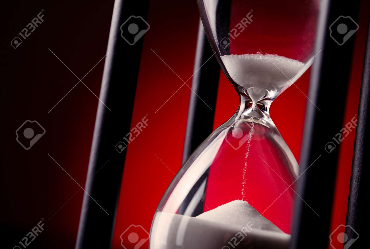 Egg timer or hourglass on a graduated red background in a conceptual image of passing time and time management - 30749958