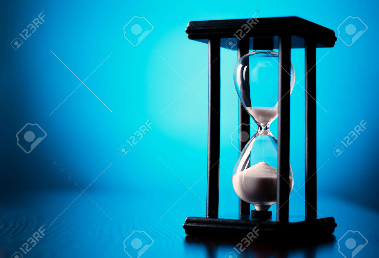 Egg timer or hourglass on a graduated blue background with copyspace in a conceptual image of passing time and time management - 30765356