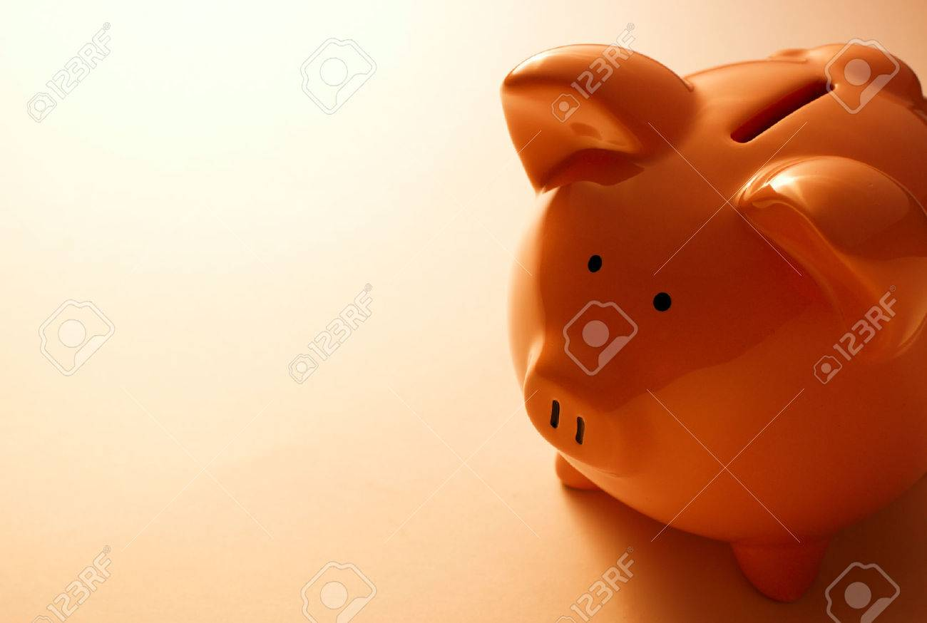 Backlit pink ceramic piggy bank standing facing the camera in a financial, savings and investment concept - 30977210