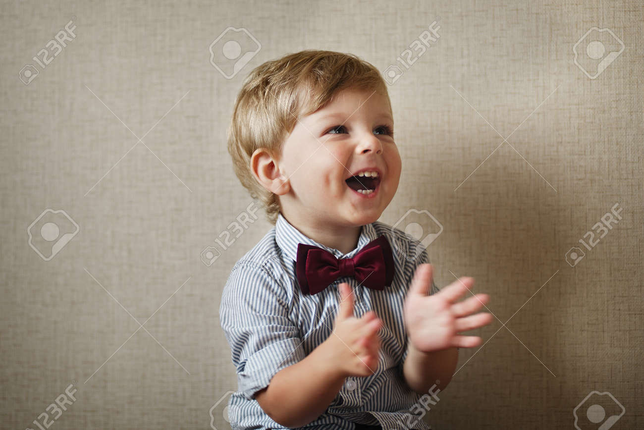 Beautiful little boy wearing a stylish maroon bow tie laughing and clapping his hands against a grey wall with vignetting - 31843072
