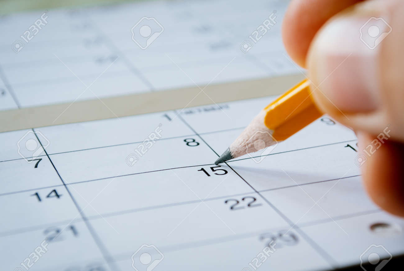 Person marking the date of the 15th with a pencil on a blank calendar with date squares as a reminder of an important day or to schedule a meeting or event - 32607431