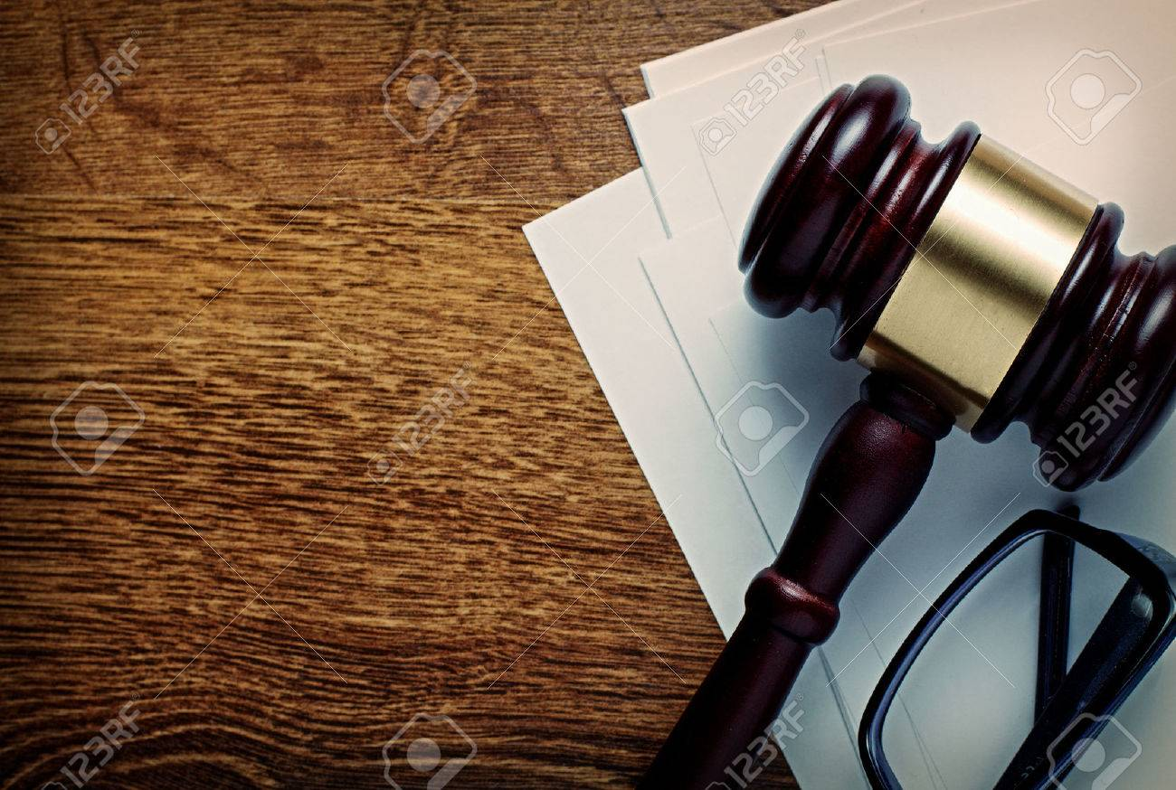 Wooden gavel with a brass band and glasses on notepaper conceptual of a judgement in law, justice or an auctioneers gavel, view from above on a wooden desk with copyspace - 34102683