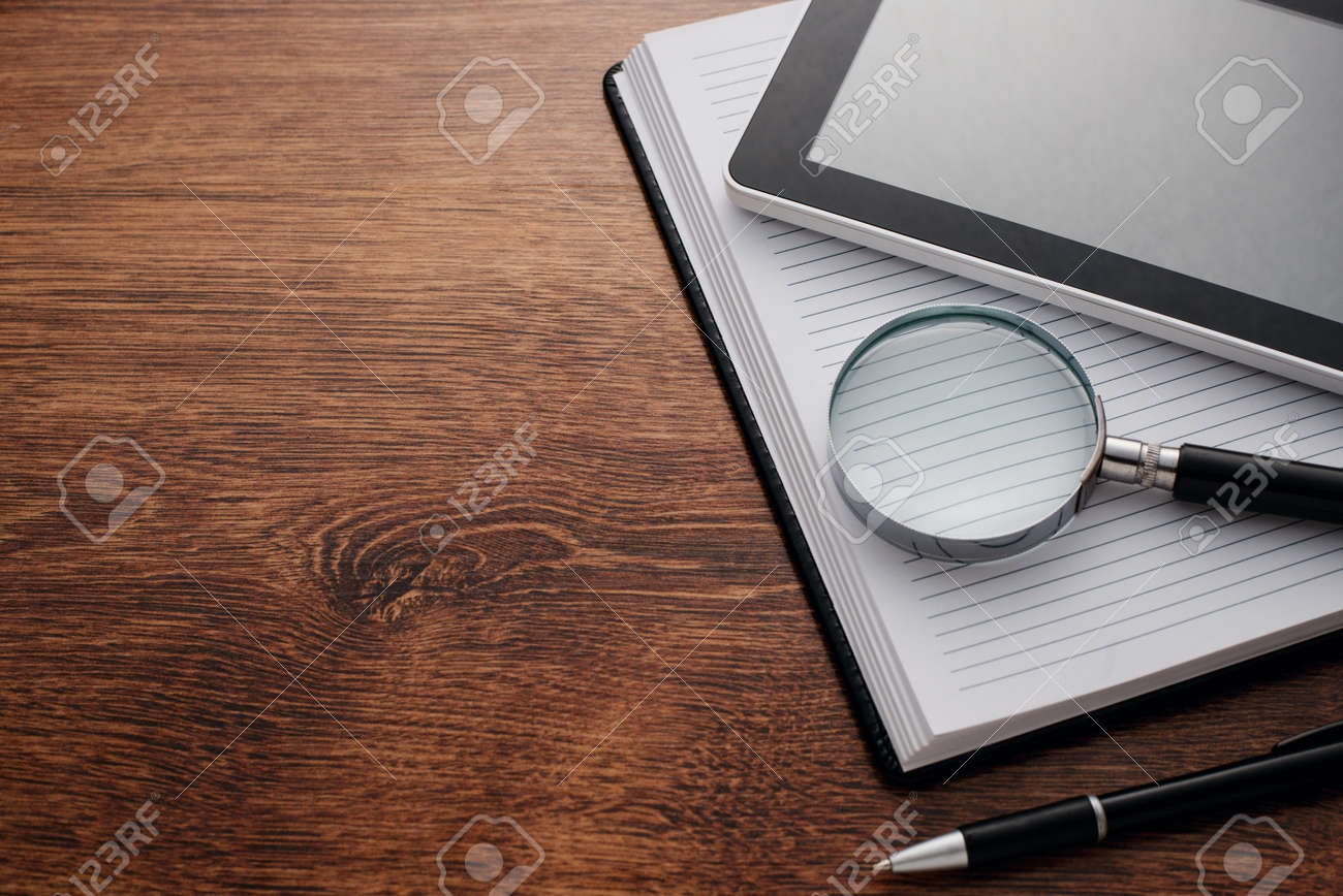 Close up Tablet Gadget and Magnifying Glass on Top of Open Notes, Resting on Wooden Table at the Right Edge, with Copy Space on Left Side for Texts. - 34103209