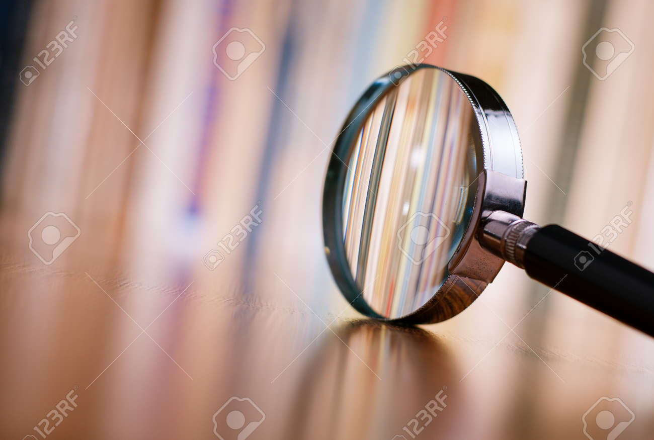 Close up Single Magnifying Glass with Black Handle, Leaning on the Wooden Table at the Office. - 34103442