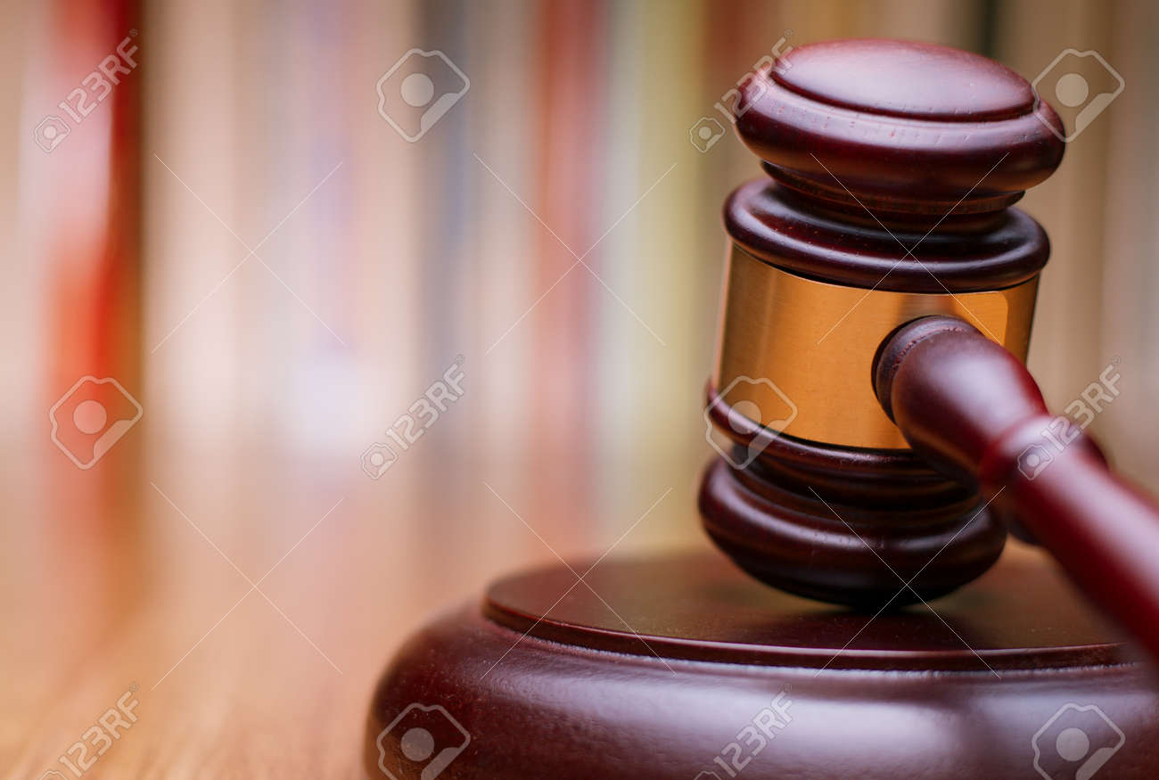 Close up Shiny Wooden Law Gavel in Dark Brown Color, on Top of Wooden Table at the Office. - 34104183