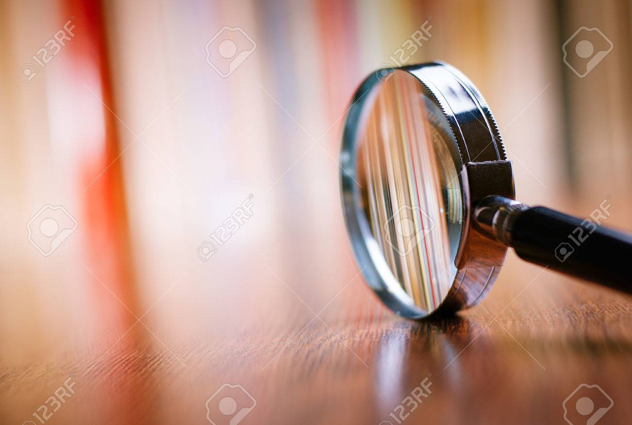 Close up Single Magnifying Glass with Black Handle, Leaning on the Wooden Table at the Office. - 34105449