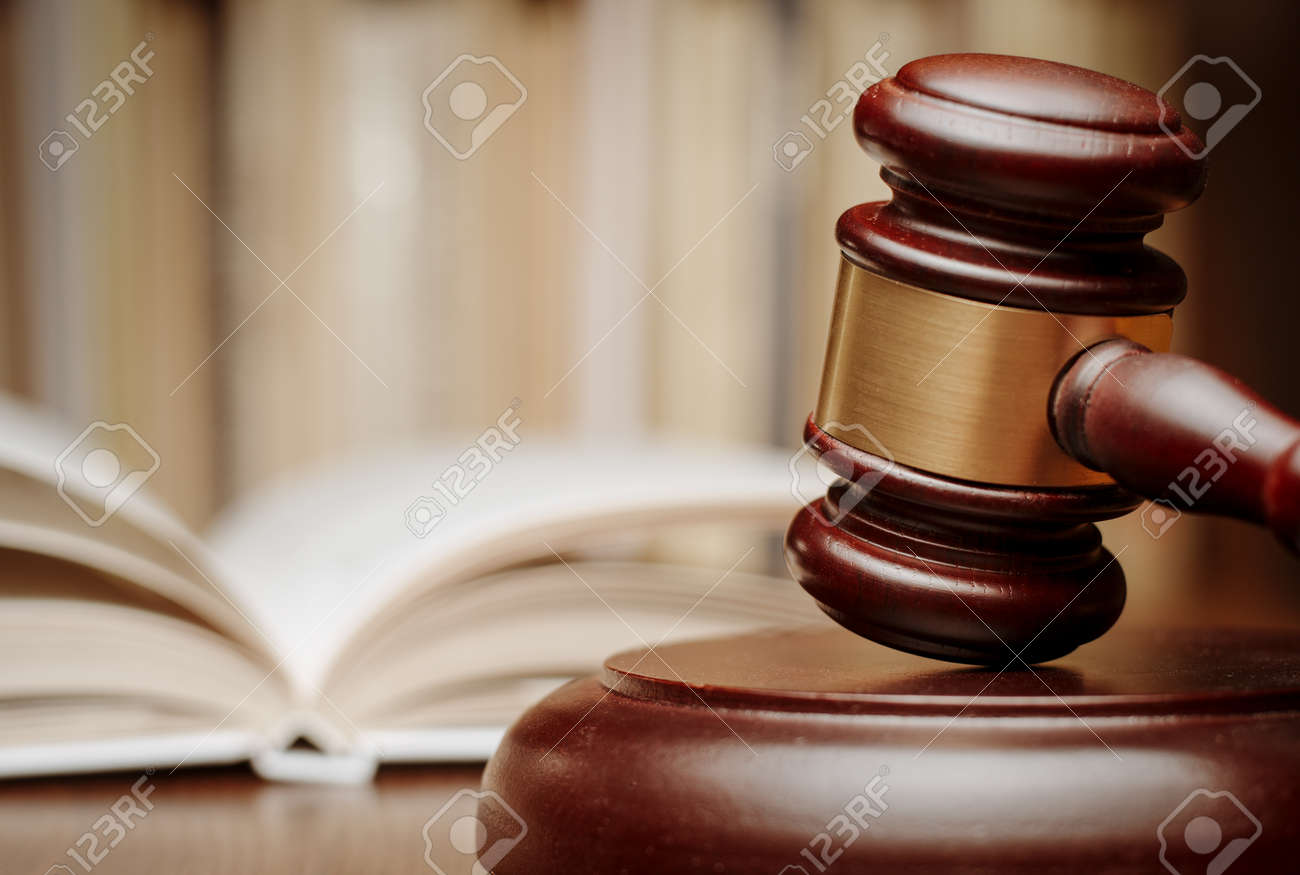Wooden gavel resting on its end on a wooden table in front of an open law book conceptual of a judge, courtroom and judgements - 34864076