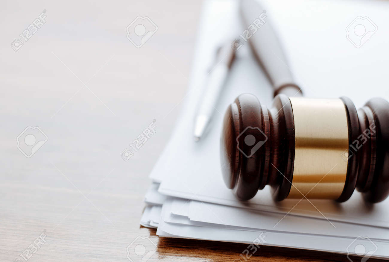 Gavel, ball pen and paper for notes lie on the wooden desk. - 34865044