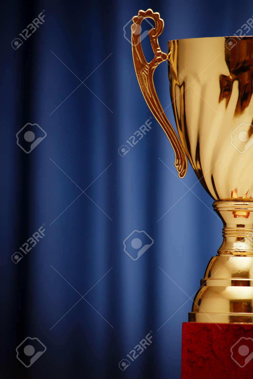 Golden glowing trophy cup on a dark blue background - 36510564
