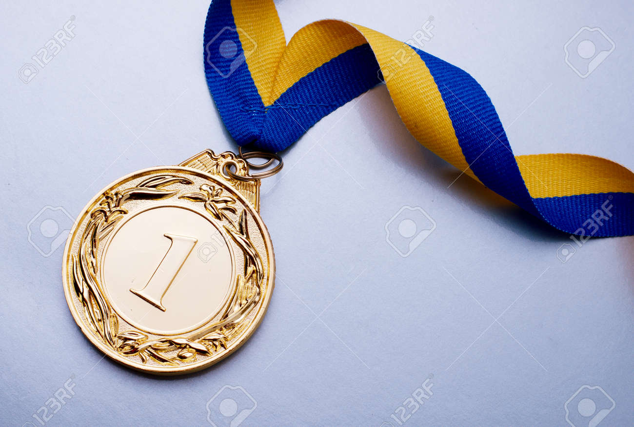 Gold medal in the foreground on yellow blue ribbon - 36510584