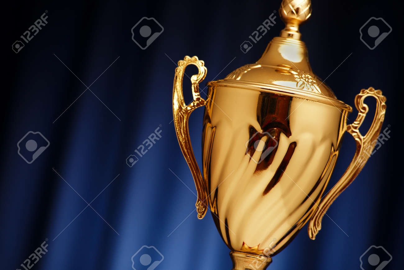 Golden glowing trophy cup on a dark blue background - 36510606