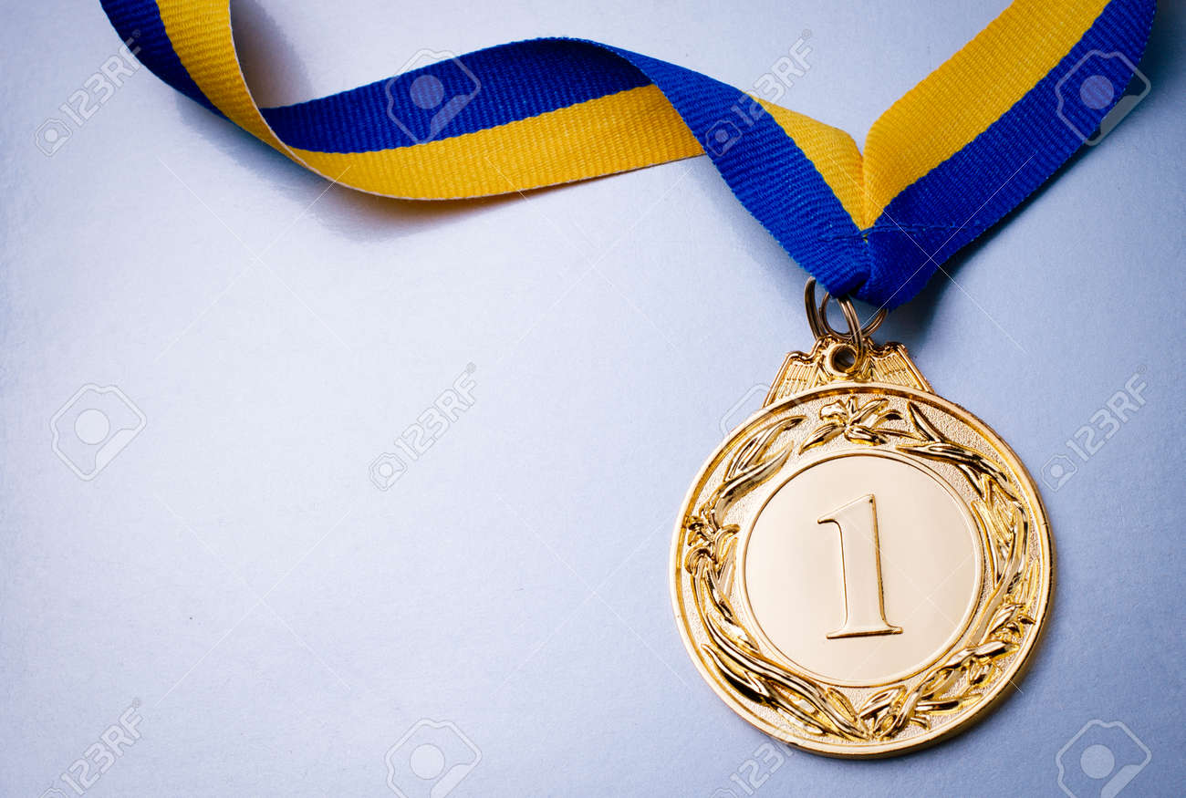 Gold medal in the foreground on yellow blue ribbon - 36510607