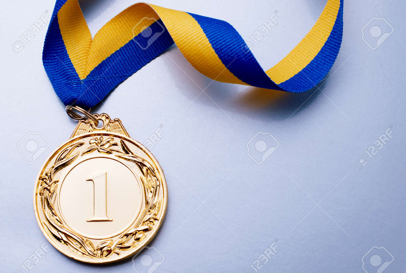 Gold medal in the foreground on yellow blue ribbon - 36510608