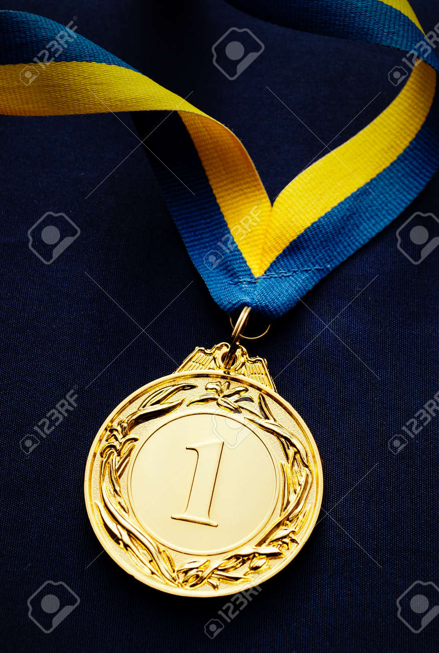 Gold medal in the foreground on yellow blue ribbon - 36510622