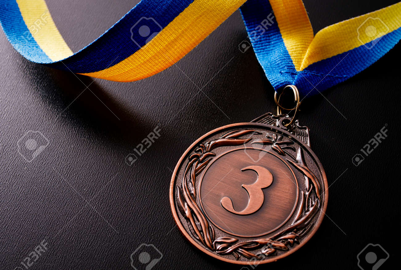 Bronze medal in the foreground on yellow blue ribbon - 36510632